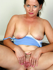 Senior woman posing nude on the carpet